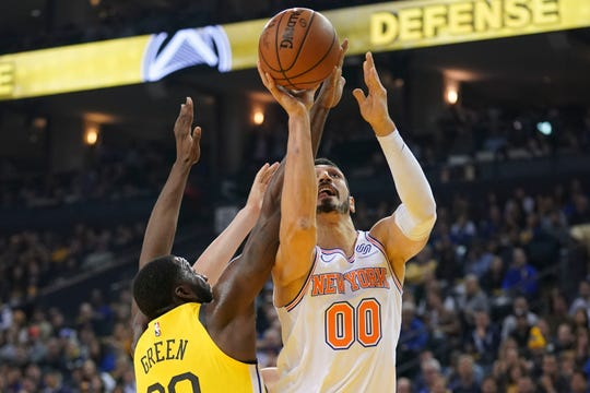 January 8, 2019; Oakland, CA, USA; New York Knicks center Enes Kanter (00) shoots the basketball against Golden State Warriors forward Draymond Green (23) during the first quarter at Oracle Arena.