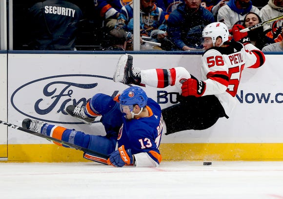 Jan 17, 2019; Uniondale, NY, USA; New York Islanders center Mathew Barzal (13) and New Jersey Devils left wing Blake Pietila (56) battle for the puck during the third period at Nassau Veterans Memorial Coliseum.