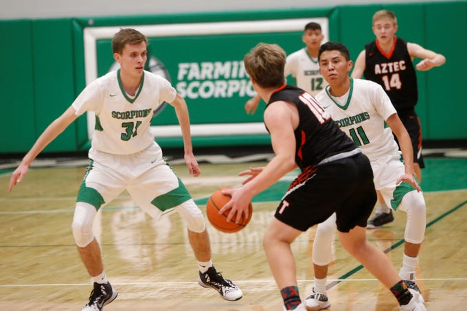 Farmington's Jacob Gillen (31) and Keyshawn Pete (11) look to get a defensive stop against Aztec's Mikey Phillips during Thursday's game at Scorpion Arena in Farmington.