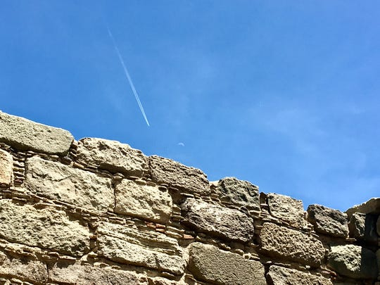 Old and new are often found in the same place in New Mexico. This wall in the Salmon Ruins complex in Bloomfield is seen in this 2017 file photo below a partial moon and a jet contrail.