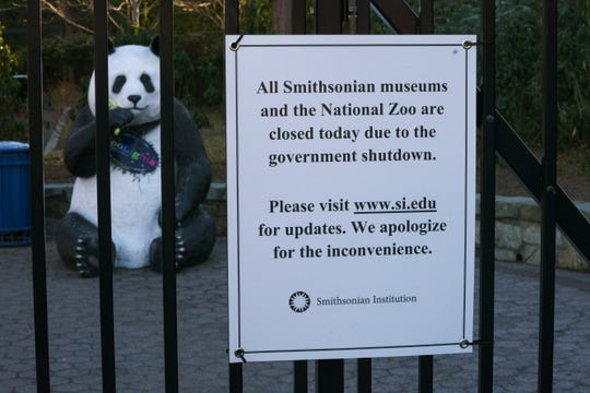In this Friday, Jan. 11, 2019, photo a statue of a panda bear is seen behind the gate of the Smithsonian's National Zoo that is closed because of the partial government shutdown in Washington.