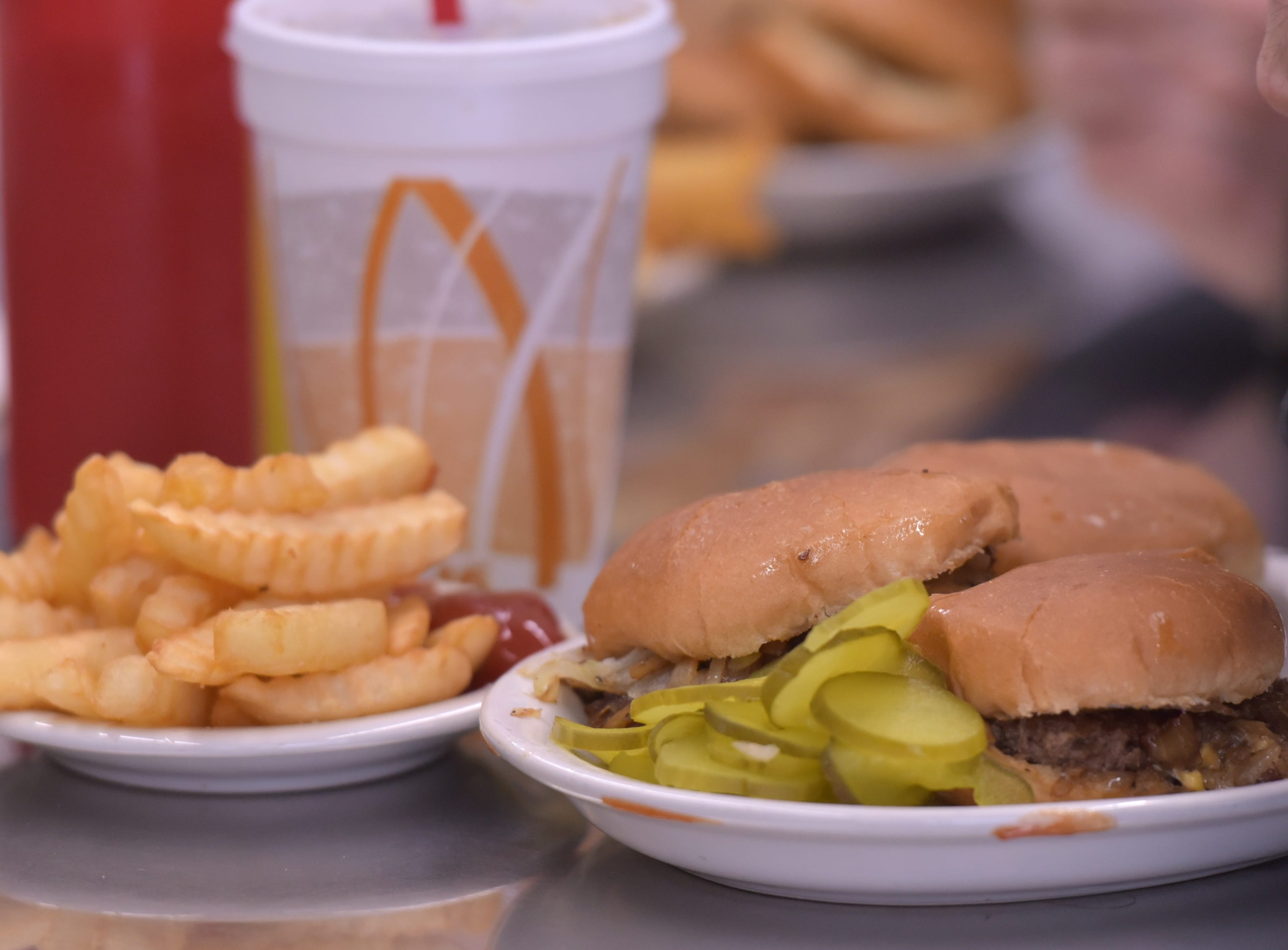 A wonderful sight at Bates Burgers: a plate with three cheeseburgers with onions and pickles and those krinkle-cut fries.