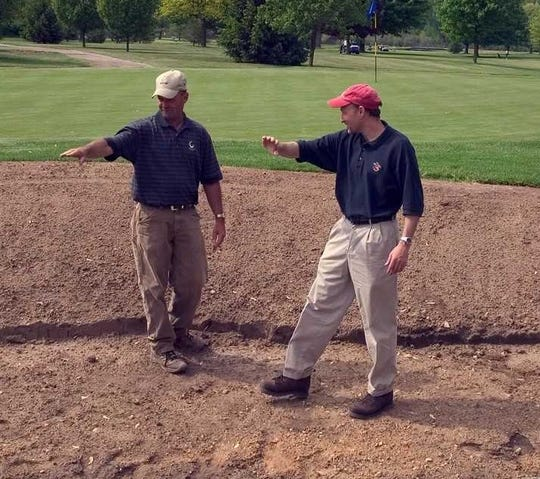 Paul Albanese (right) discusses the shape of a greenside bunker with a colleague.