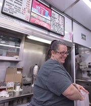 Mary Ann Brent, a five-year Bates Burger employee, smiles as she packs another to-go order during a busy Thursday lunch time rush. Bates will celebrate its 60th anniversary in February.
