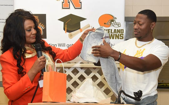 Center for Academic Programs principal Cynthia Richard presents Christian Boutte with a school T-Shirt after he spoke to the students Thursday morning. Boutte, an Opelousas High School graduate and outstanding football player is now a member of the Cleveland Browns in the National Football League.