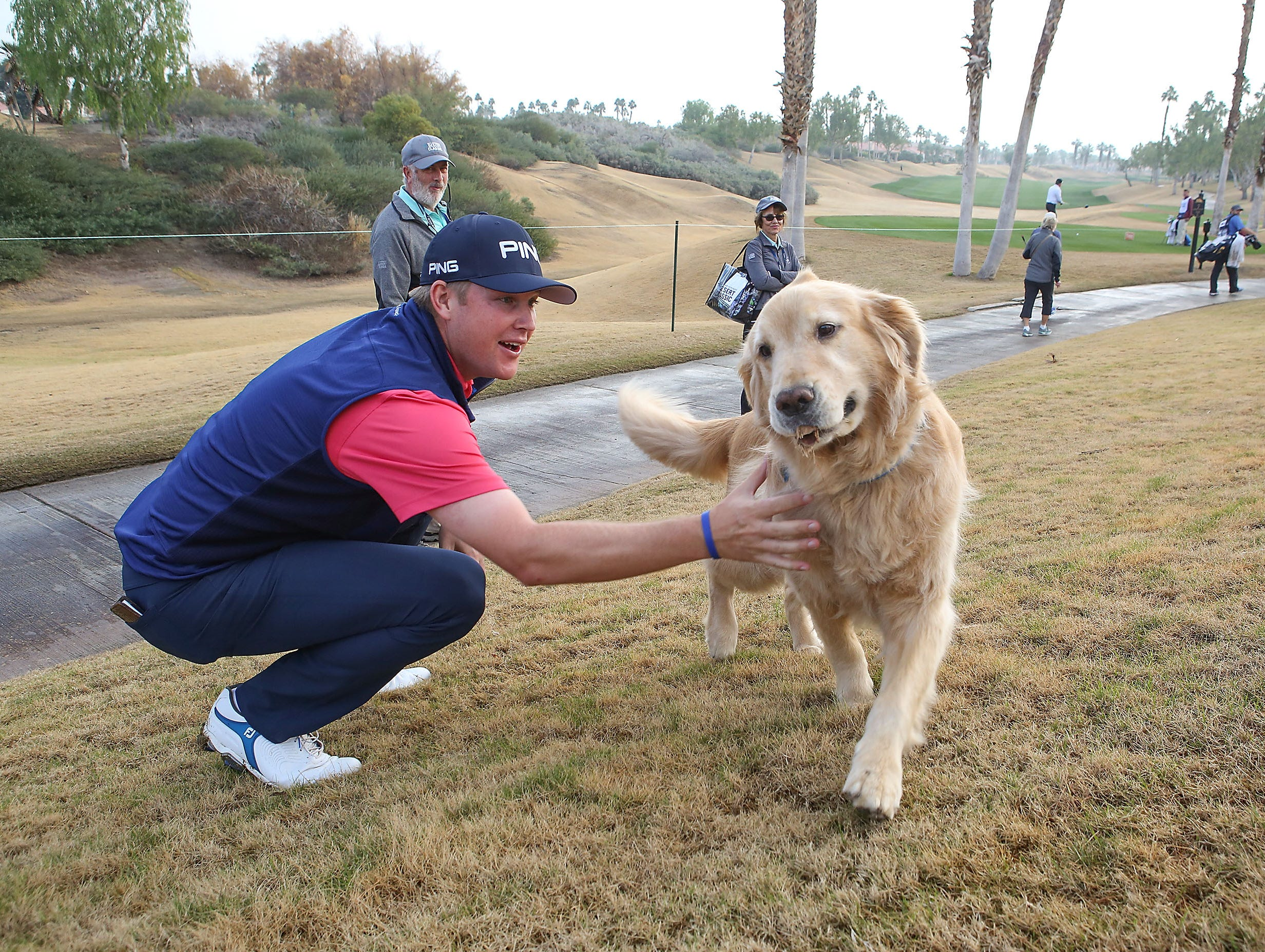 Trey Mullinax meets a friendly dog named Beauregard before teeing off on the 7th hole of the Nicklaus Tournament Course at PGA West, January 17, 2019.