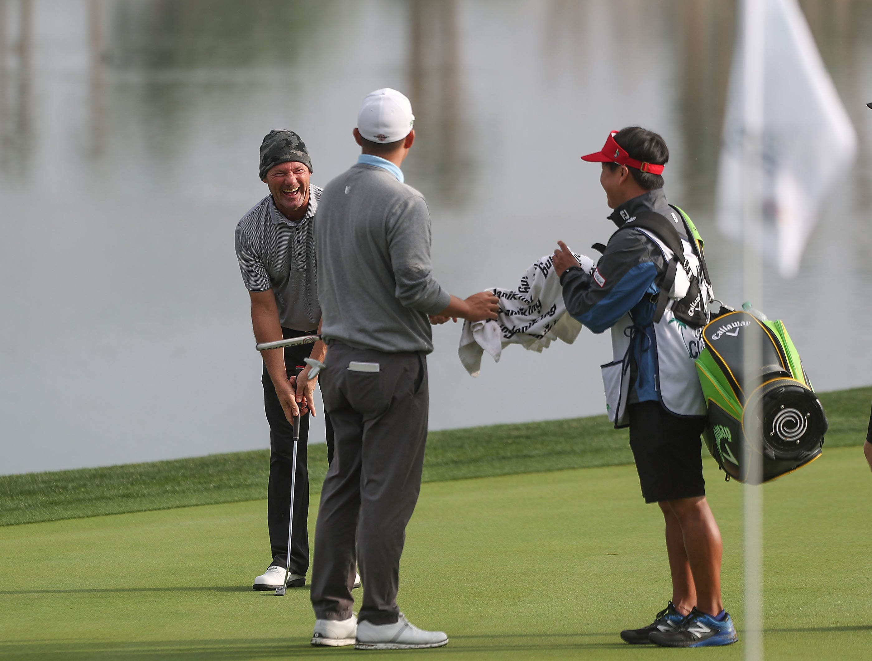 Alex Cejka, left, laughs on the 18th green with John Huh center during the Desert Classic at PGA West, January 17, 2019.