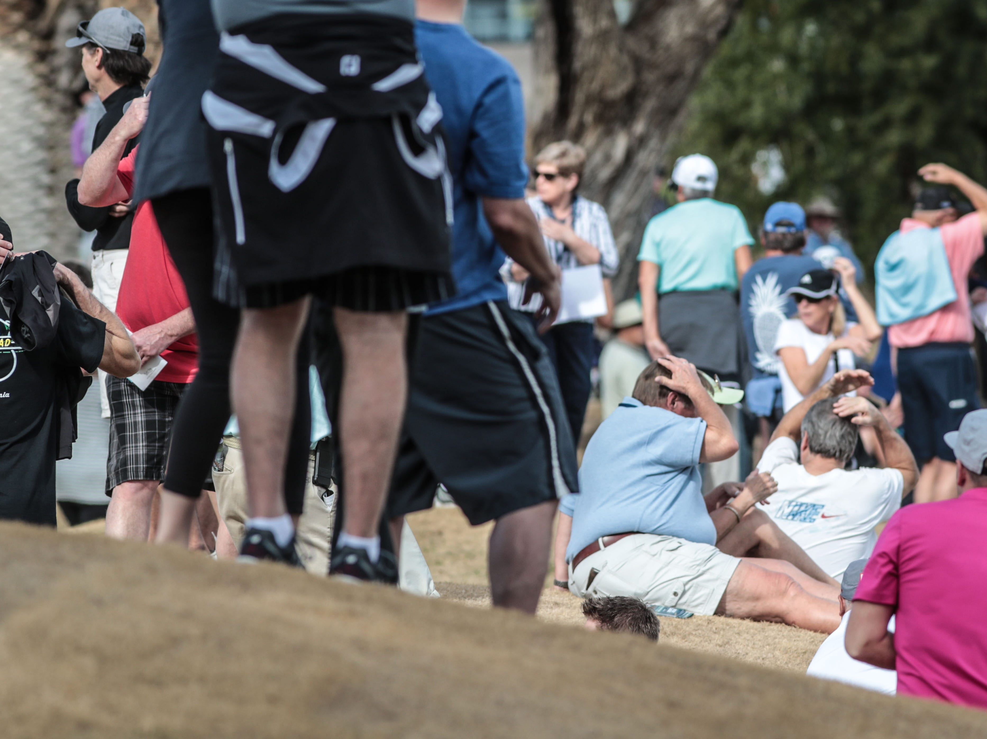 Spectators cover their heads as Phil Mickelson's 18th tee shot lands in the cart path at the Nicklaus Tournament Course at PGA West in La Quinta during the 2nd round of the Desert Classic on Friday, January 18, 2019.