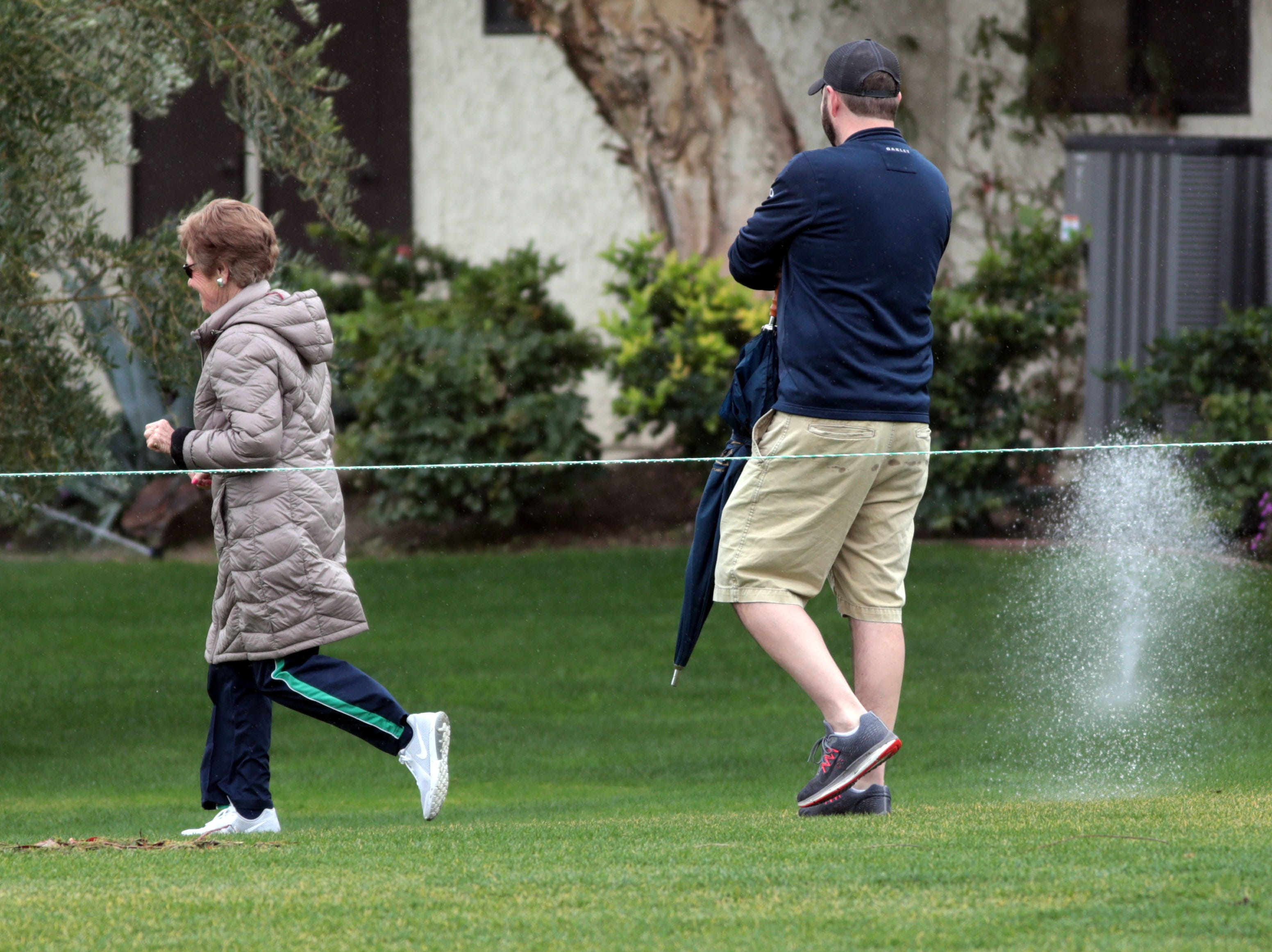 Fans runaway as sprinklers goes off in the rain at La Quinta County Club during the 1st round of the Desert Classic on Thursday, January 17, 2019.