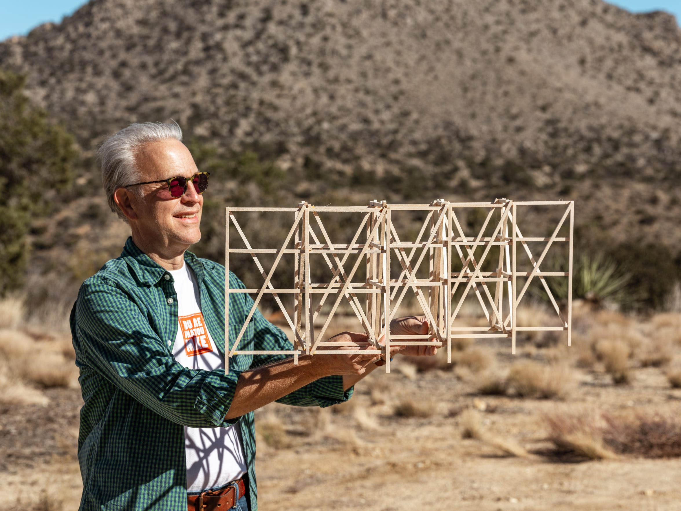 Makerville Studio founder Richard Hovel holds a small-scale version of the wooden structure that will serve as the foundation for Looming Shelter, a parallel project during Desert X 2019.