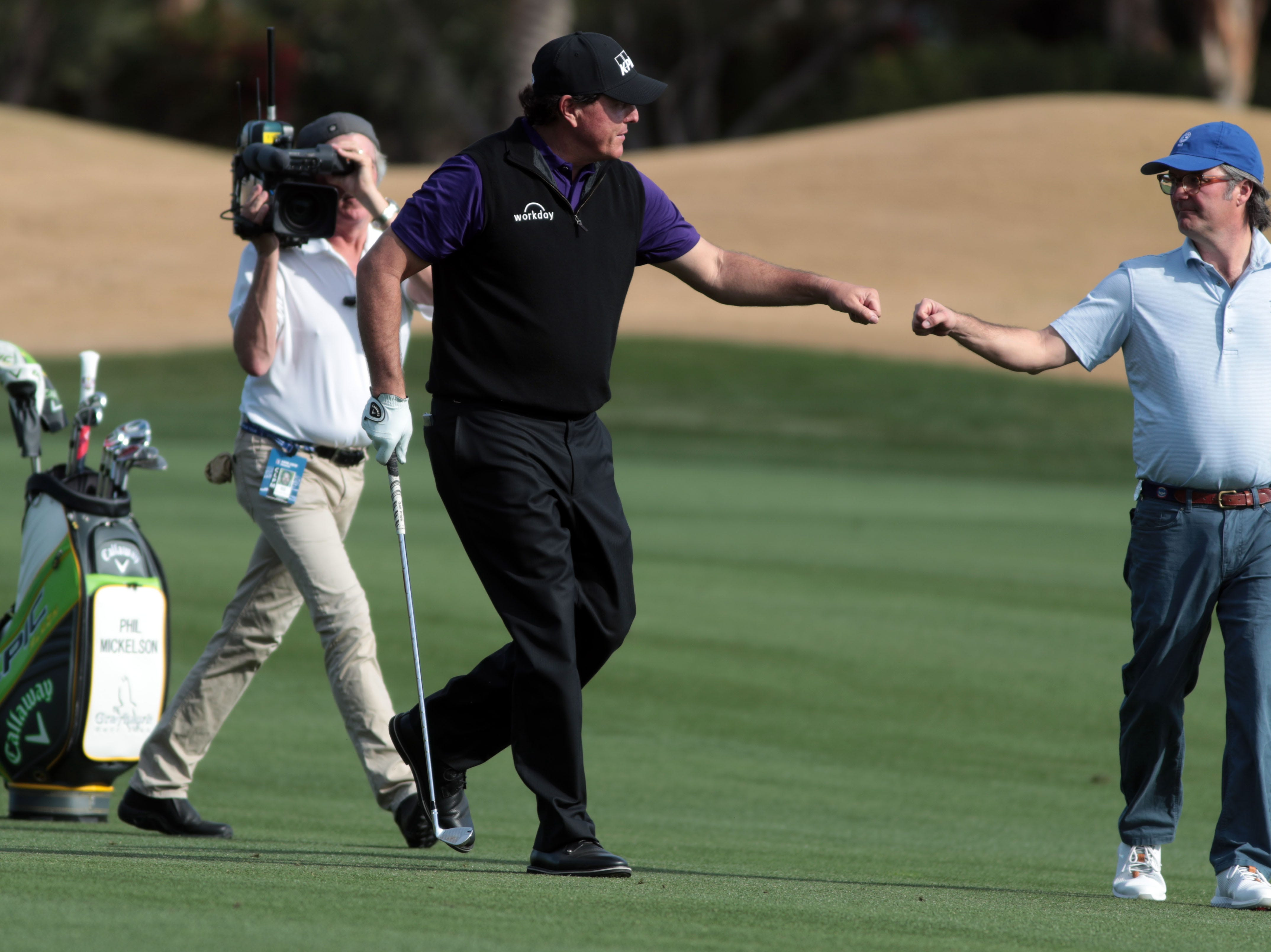 Phil Mickelson, after hitting his approach shot on 9, fist bumps Andy Blackburn on the Nicklaus Tournament Course at PGA West in La Quinta during the 2nd round of the Desert Classic on Friday, January 18, 2019.