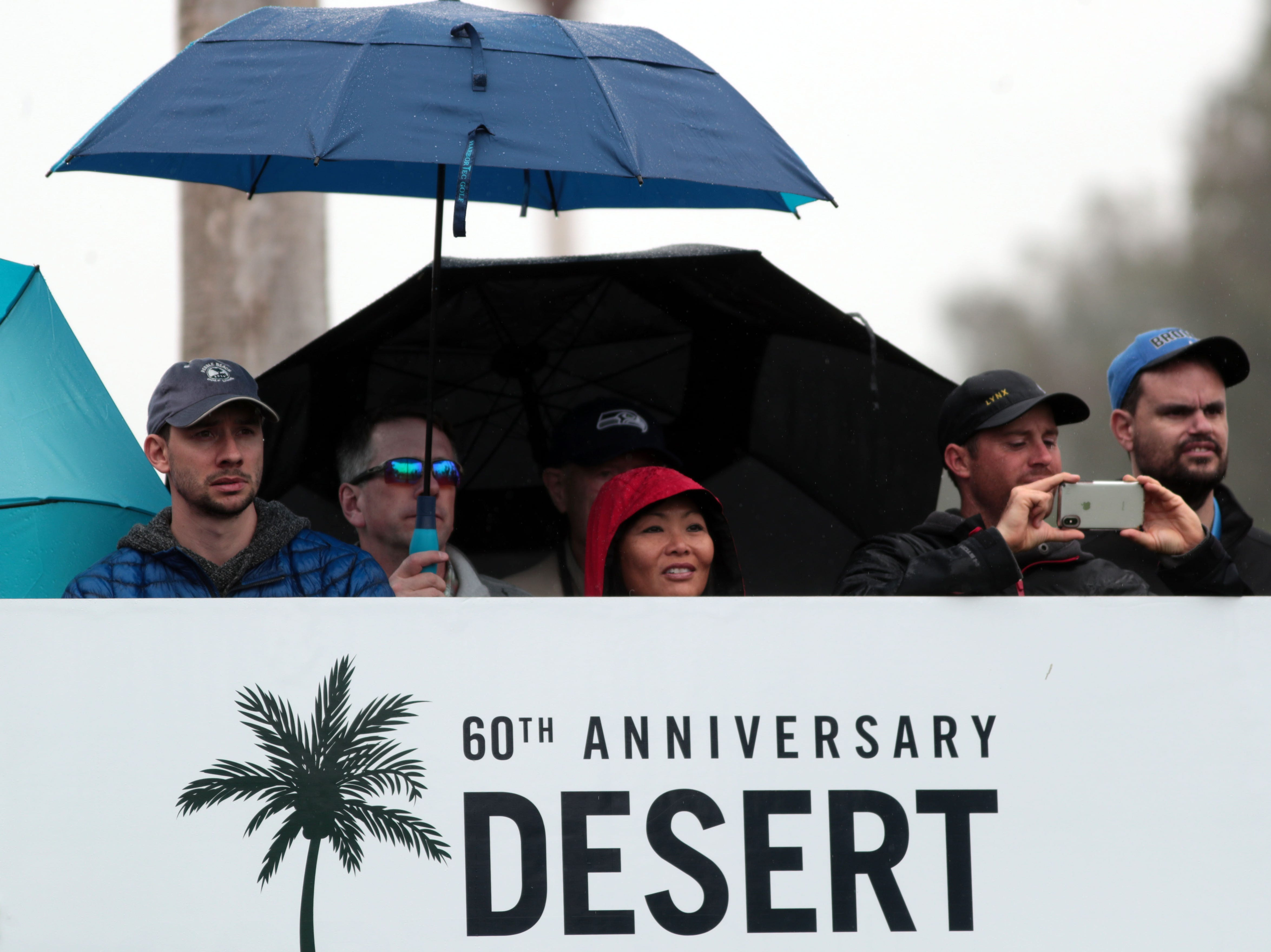 Fans brave the rain to watch Justin Rose tee off on 9 at La Quinta County Club during the 1st round of the Desert Classic on Thursday, January 17, 2019.