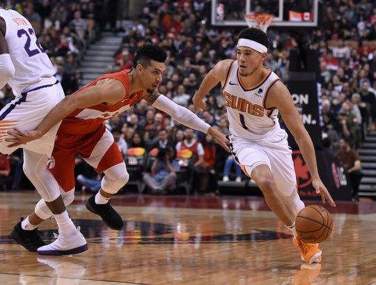 Jan 17, 2019; Toronto, Ontario, CAN;  Phoenix Suns guard Devin Booker (1) dribbles the ball around Toronto Raptors guard Danny Green (14) in the first half at Scotiabank Arena. Mandatory Credit: Dan Hamilton-USA TODAY Sports