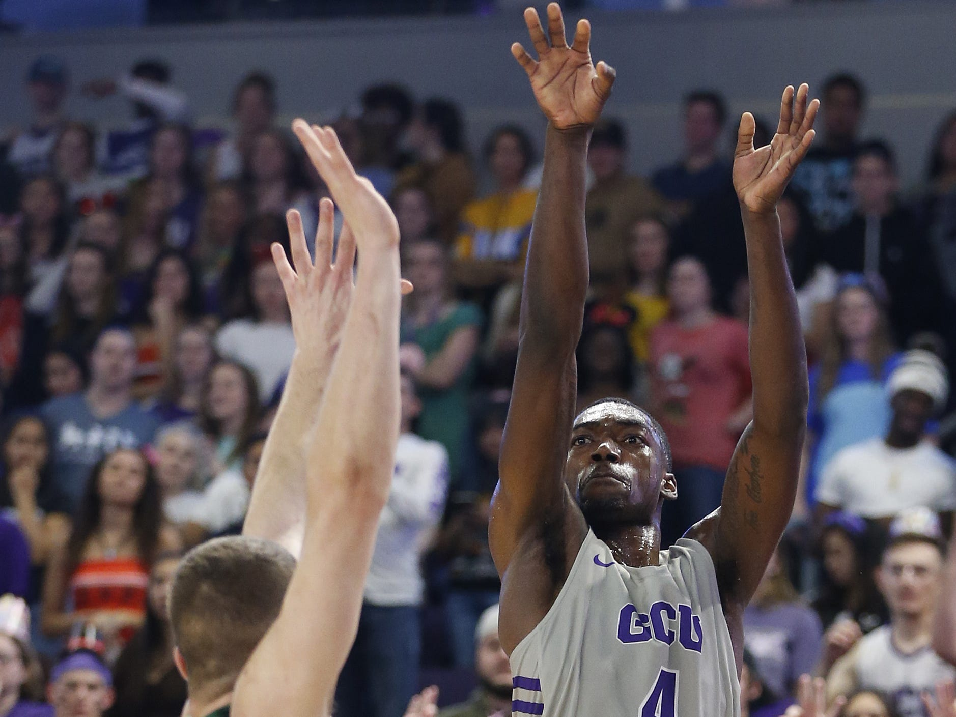 GCU's Oscar Frayer (4) shoots a three pointer against Chicago State University's Patrick Szpir (23) during the first half at Grand Canyon University Arena in Phoenix, Ariz. on January 17, 2019.
