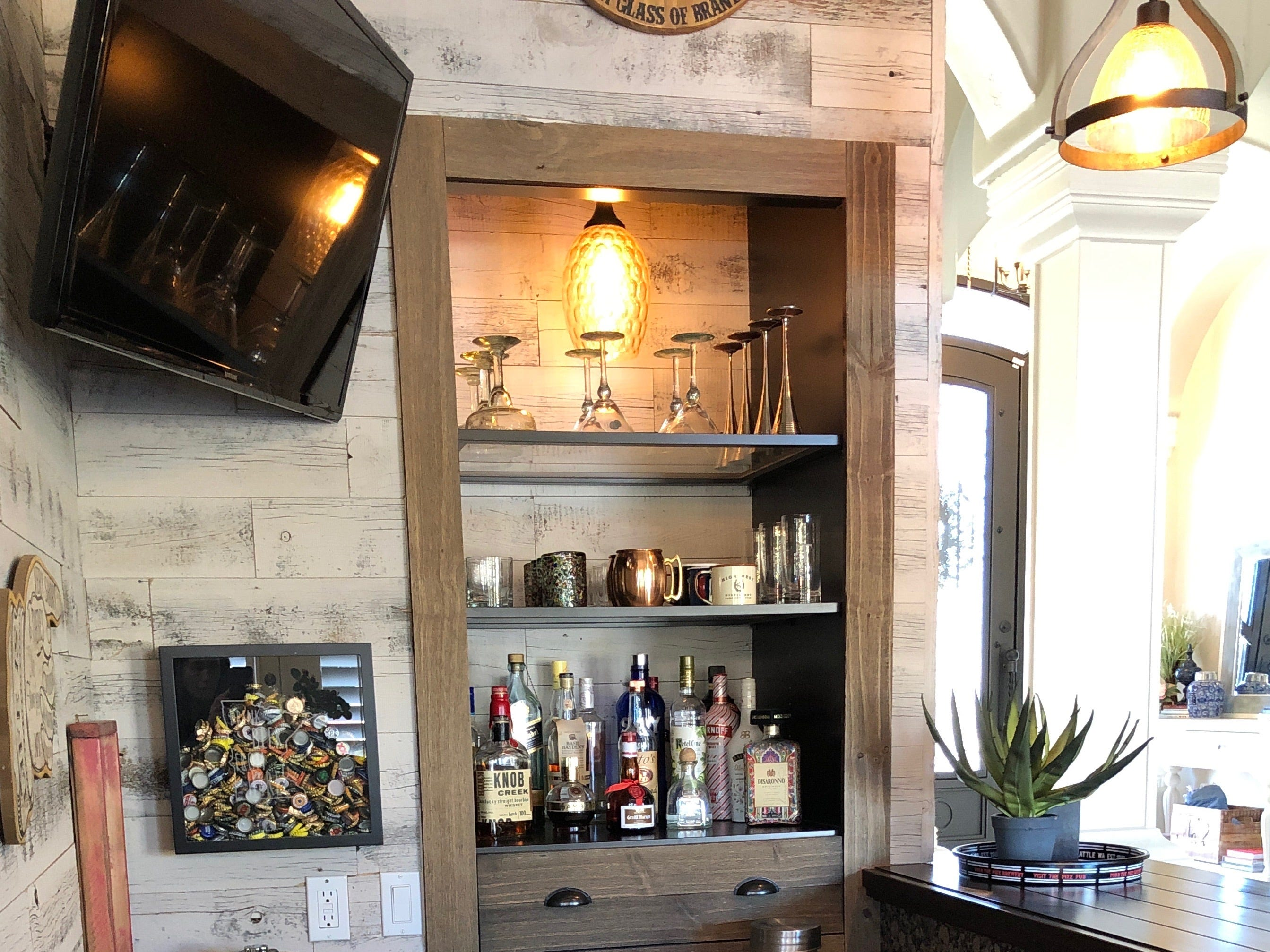 An Ikea closet was transformed into a storage cubby for liquor and glasses. The idea came from Mark Hutchinson, a personal friend who does remodeling work on the side.