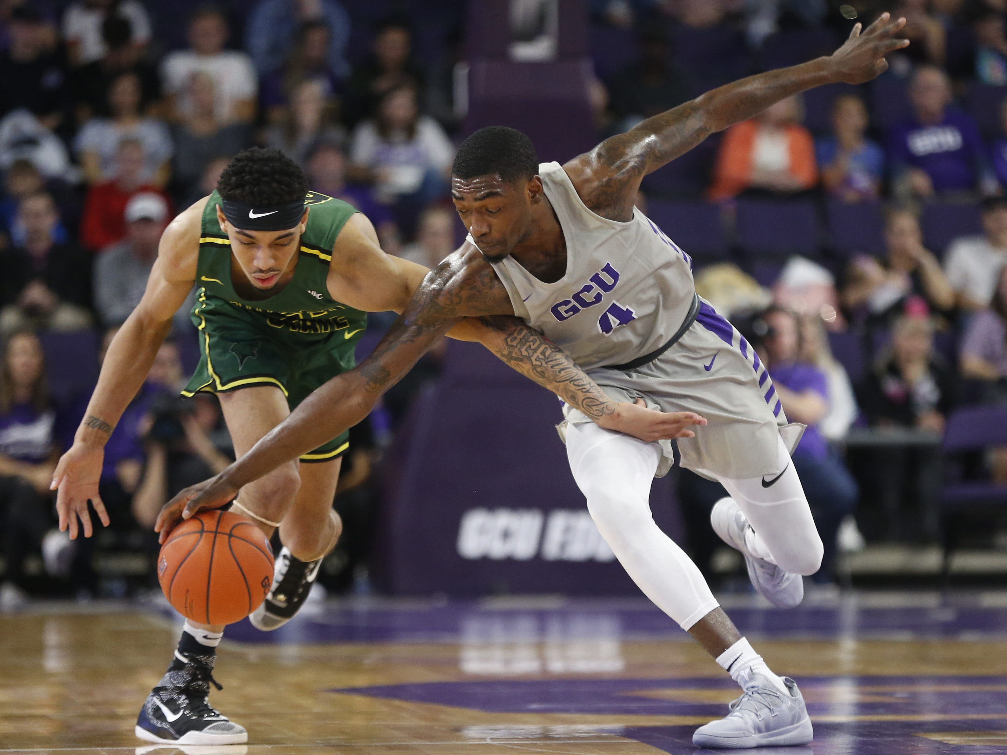 GCU's Oscar Frayer (4) steals a ball away from Chicago State University's Cameron Bowles (21) during the first half at Grand Canyon University Arena in Phoenix, Ariz. on January 17, 2019.