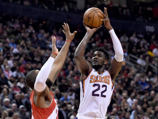 Jan 17, 2019; Toronto, Ontario, CAN;  Phoenix Suns center Deandre Ayton (22) shoots over Toronto Raptors center Greg Monroe(15) in the first half at Scotiabank Arena. Mandatory Credit: Dan Hamilton-USA TODAY Sports