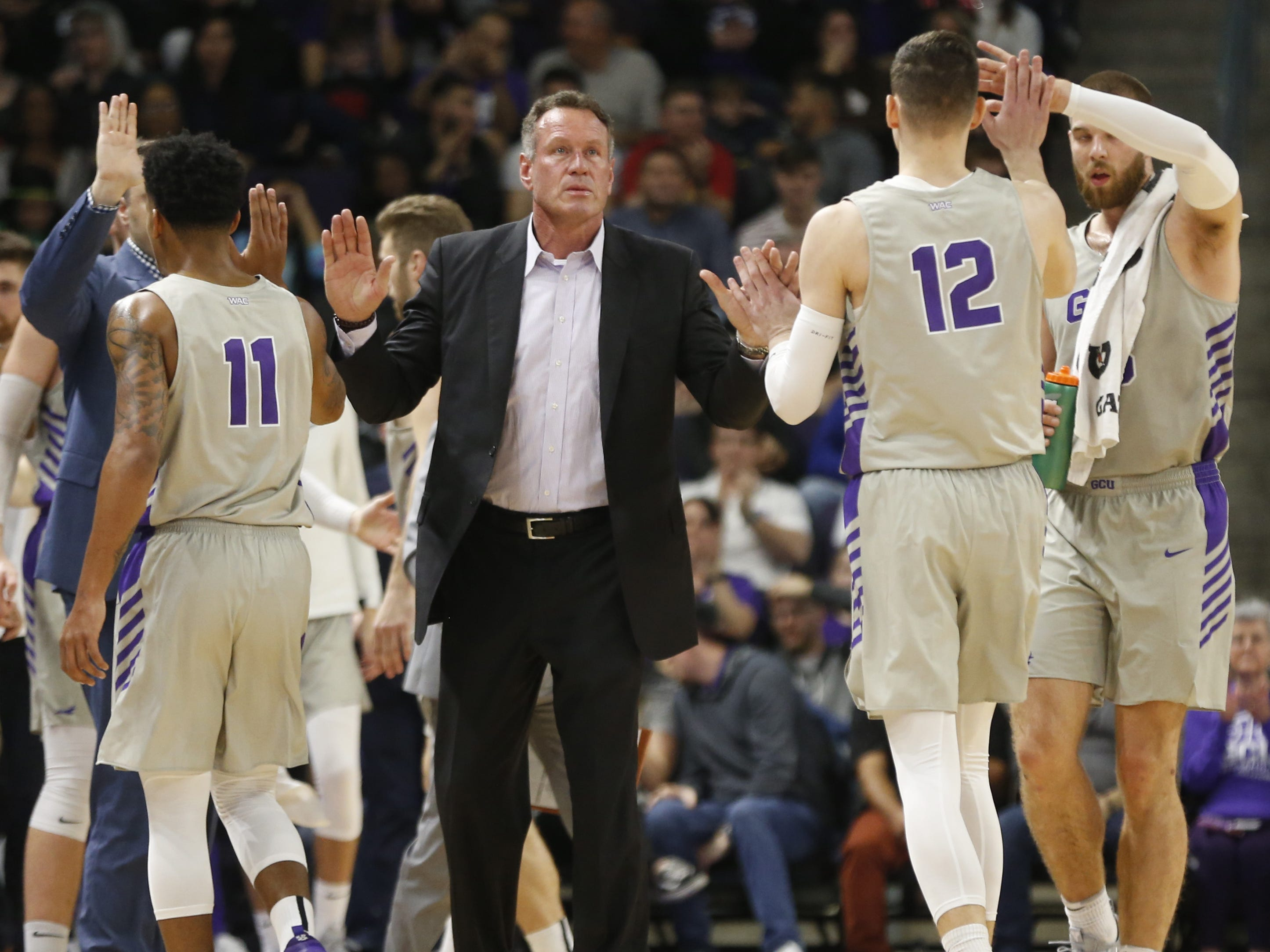GCU's head coach Dan Majerle high-fives his team as they return to a timeout against Chicago State University during the first half at Grand Canyon University Arena in Phoenix, Ariz. on January 17, 2019.