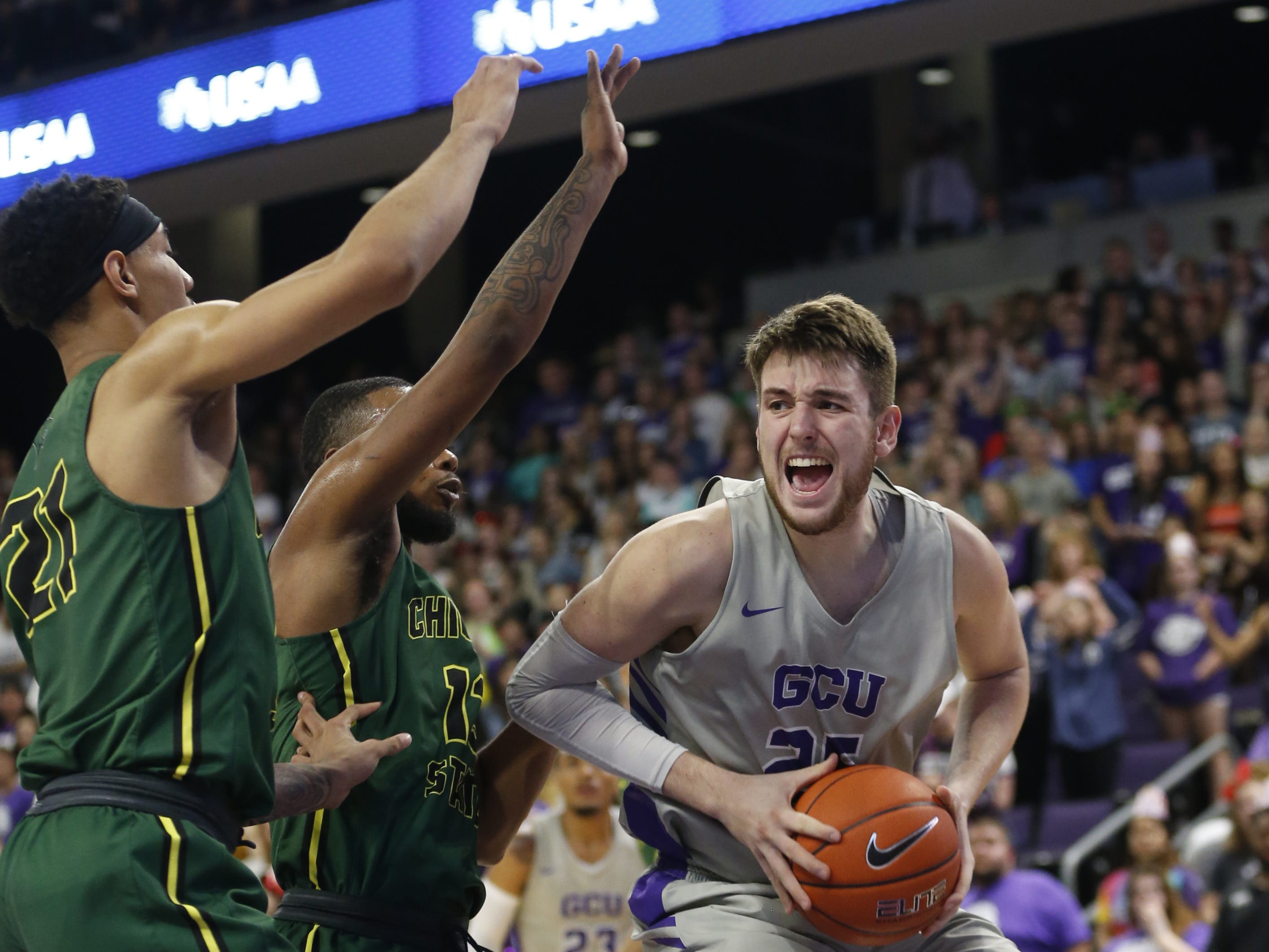 GCU's Alessandro Lever (25) drives into the post against Chicago State University's Christian Jacob (13) during the first half at Grand Canyon University Arena in Phoenix, Ariz. on January 17, 2019.