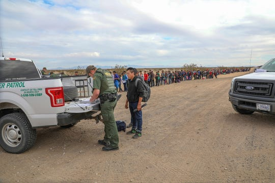 Border Patrol agents process 376 mostly Guatemala migrants seeking asylum in the U.S. after they tunneled under the border fence on Jan. 14 near the San Luis port of entry.