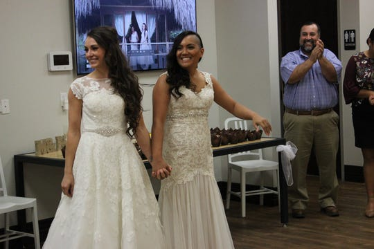 Newly married Michelle and Mimi Refuerzo enter their wedding reception.