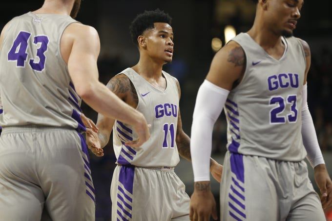 GCU's Damari Milstead (11) high-fives teammates after scoring and drawing a foul against Chicago State University during the first half at Grand Canyon University Arena in Phoenix, Ariz. on January 17, 2019.