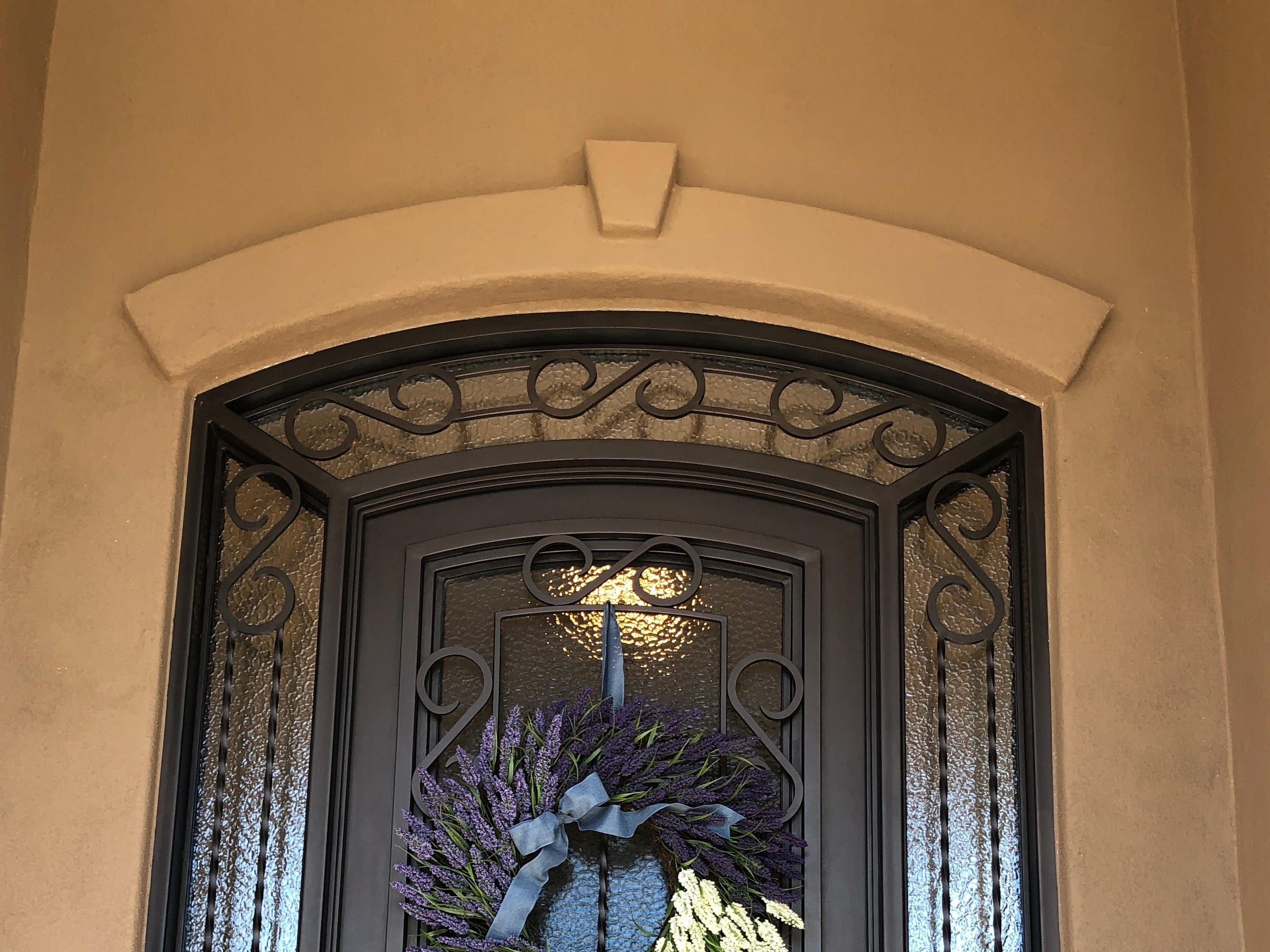 This custom iron door features a frosted glass inset that opens independently and allows for natural light.