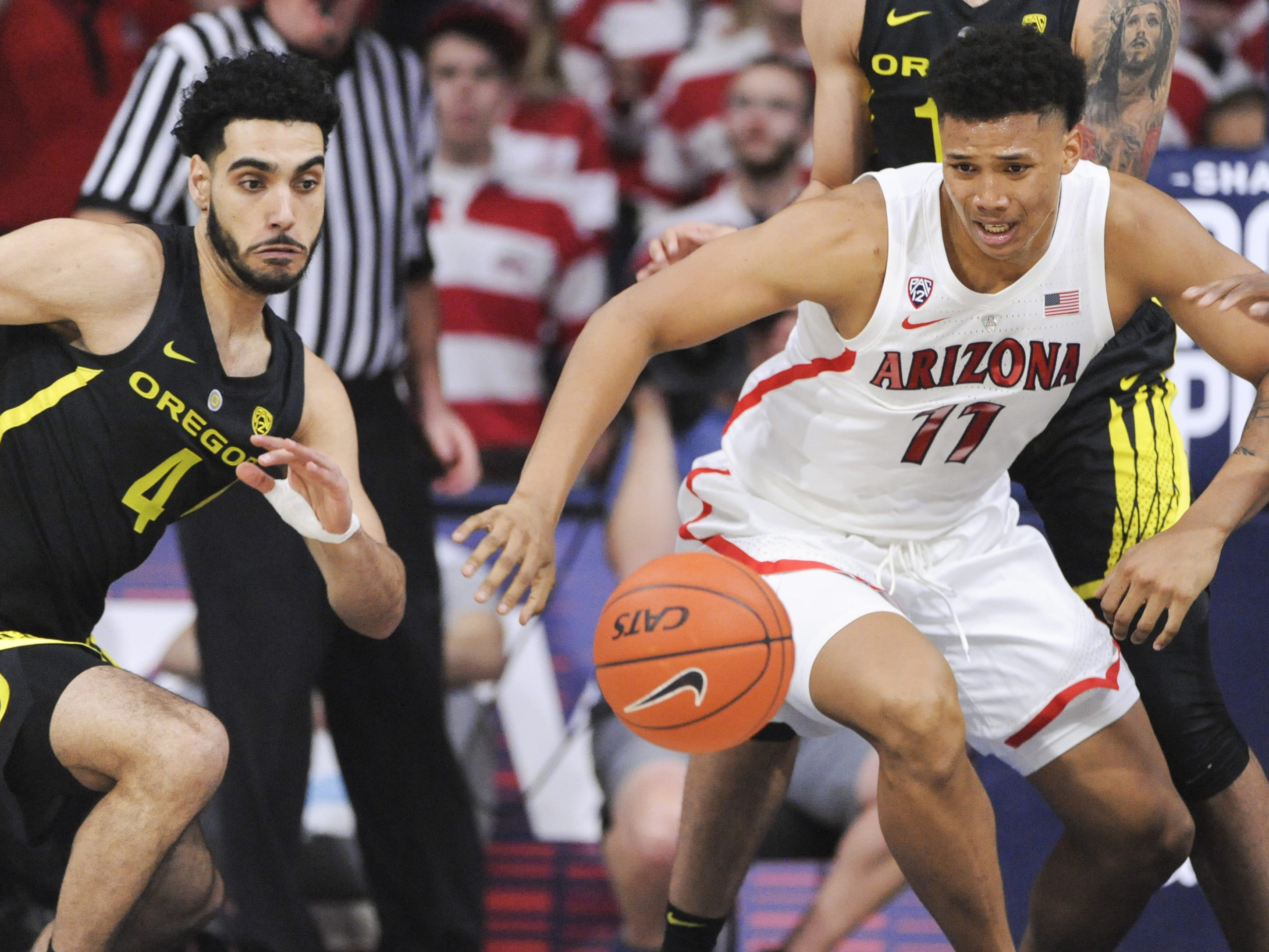 Jan 17, 2019; Tucson, AZ, USA; Oregon Ducks guard Ehab Amin (4) and Arizona Wildcats forward Ira Lee (11) chase after a loose ball during the first half at McKale Center. Mandatory Credit: Casey Sapio-USA TODAY Sports