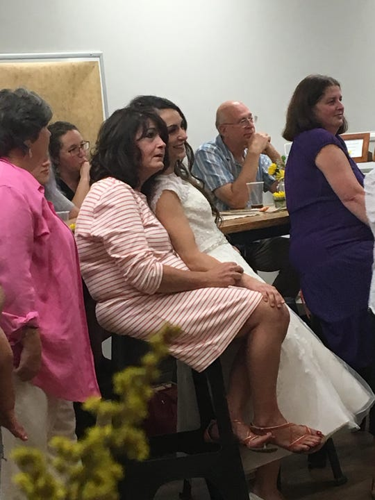 Michelle Refuerzo leans into her mother, Mary Lee LeGath as they watch her wife dance with her father at their wedding reception.