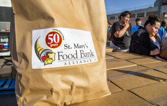 Rhoda Burbank, an employee at the Phoenix Indian Medical Center, drives through the food-box pickup outside the hospital, Friday, January 18, 2019.  Volunteer Ron Montoya, from Bank of America, right, gets information about how much food, donated by St. Mary's Food Bank, Burbank needs.  Burbank is a federal employee who hasn't received a check since December.