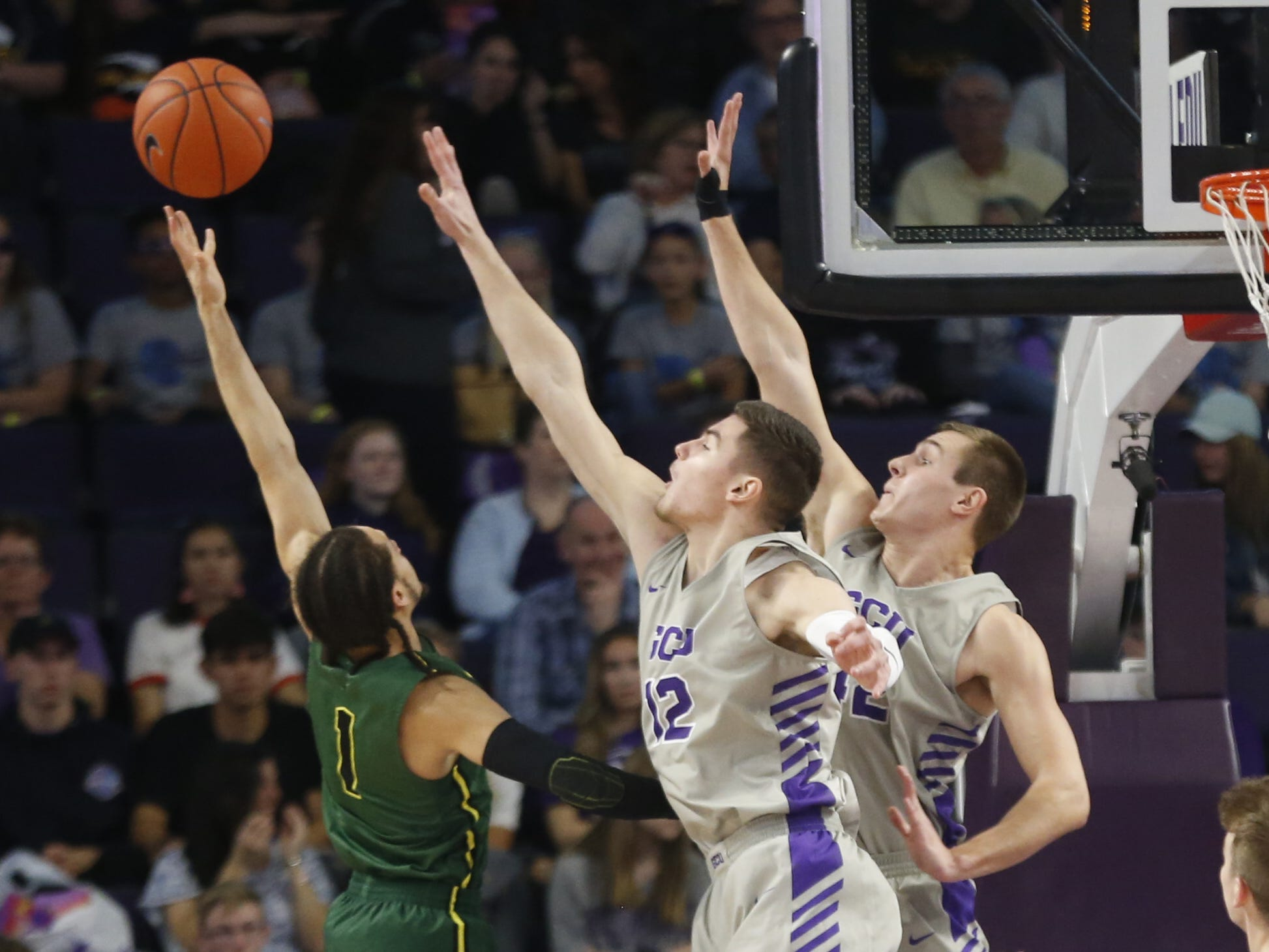 GCU's Roberts Blumbergs (12) and Gerard Martin (42) attempt to block Chicago State University's 	Rob Shaw (1) during the first half at Grand Canyon University Arena in Phoenix, Ariz. on January 17, 2019.