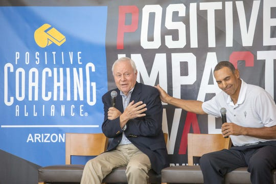 Former Arizona coach Dick Tomey, left, and ASU coach Herm Edwards share a laugh during The Positive Coaching Alliance-Arizona event last June.