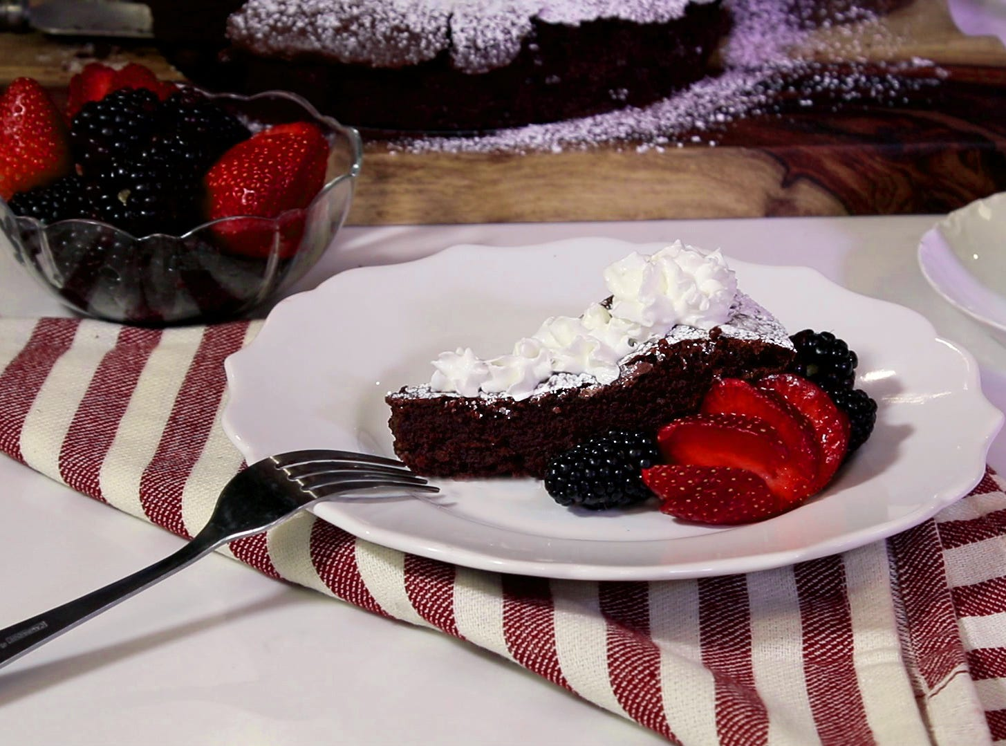 Garnish your decadent flourless chocolate cake with whipped cream and berries.