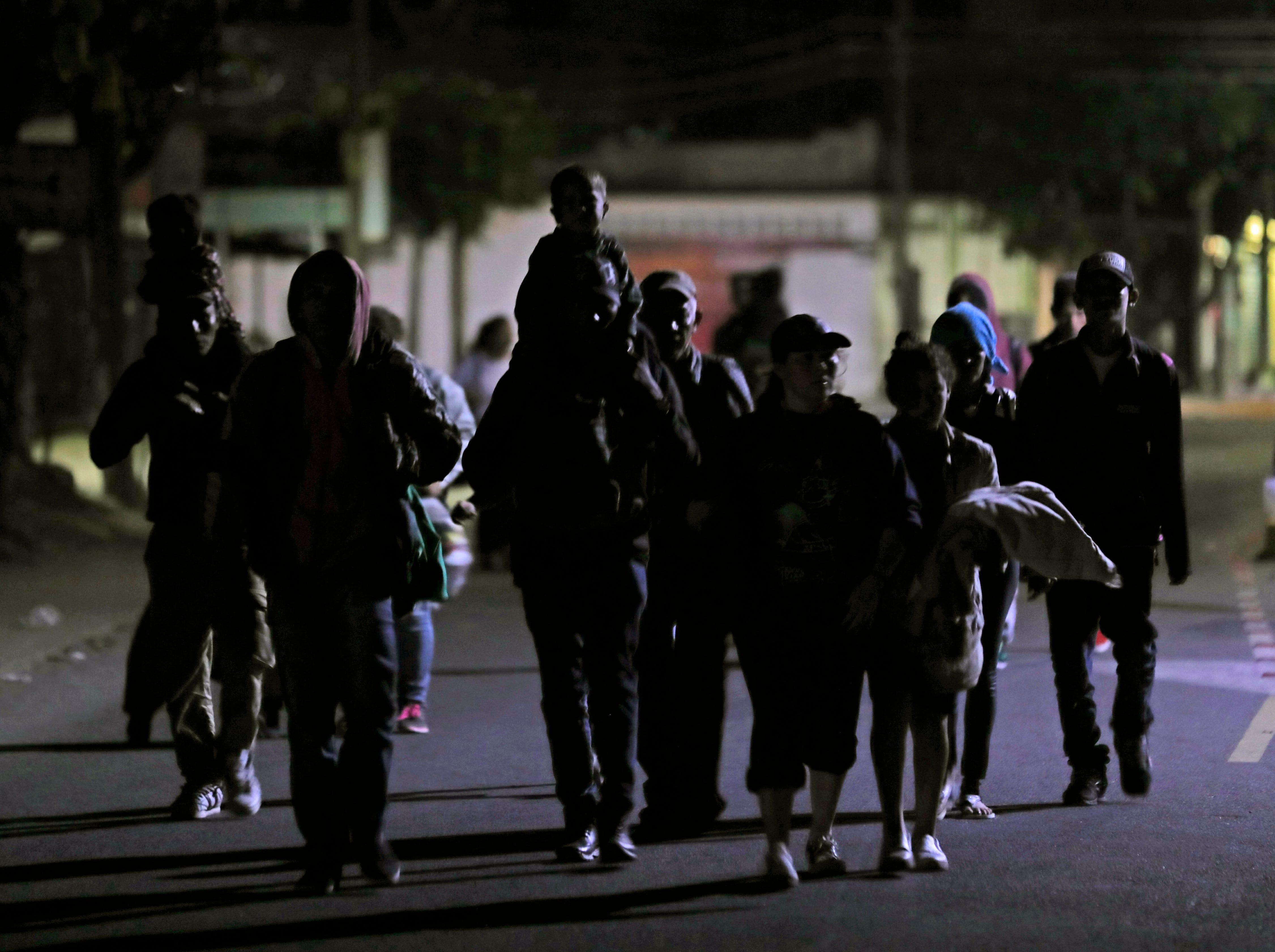 Migrantes cruzan caminando la frontera de Guatemala hacia México, la madrugada del viernes 18 de enero, 2019.