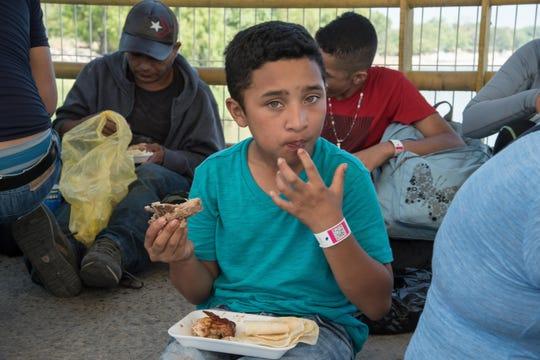 Migrantes hondureños almuerzan mientras esperan en la fila para registrarse ante las autoridades mexicanas.