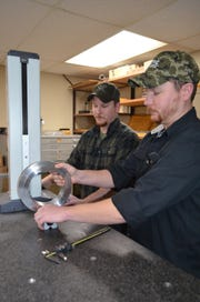 Pete Jamieson, left, and his twin brother, Tom, examine a part using a digital height gauge in the Epic Machine inspection room.
