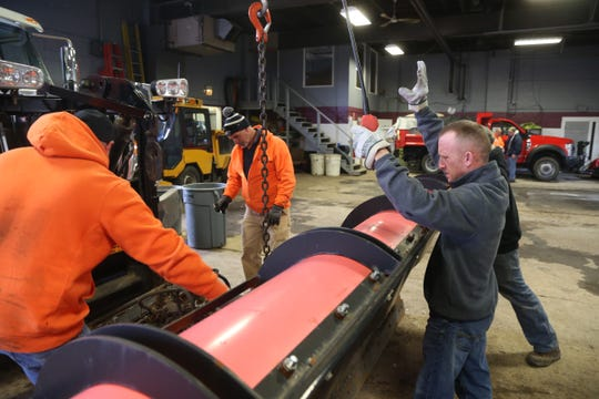 Town of Poughkeepsie deputy superintendent of highways Mike Simon, at right, signals to a driver as his crew lines up a plow onto the truck on January 18, 2019.