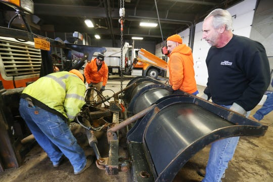 Town of Poughkeepsie Highway Department staff, from left, Jeremy Gaschel, Ken Pool, Charles Marcinelli and superintendent of highways Marc Pfeifer mount a plow onto a truck on January 18, 2019.