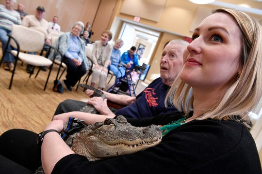 Holly Armstrong, Community Life Enrichment Director, right, and Ron Snyder, 88, cuddle with Wally the emotional support alligator, Monday, January 14, 2019.