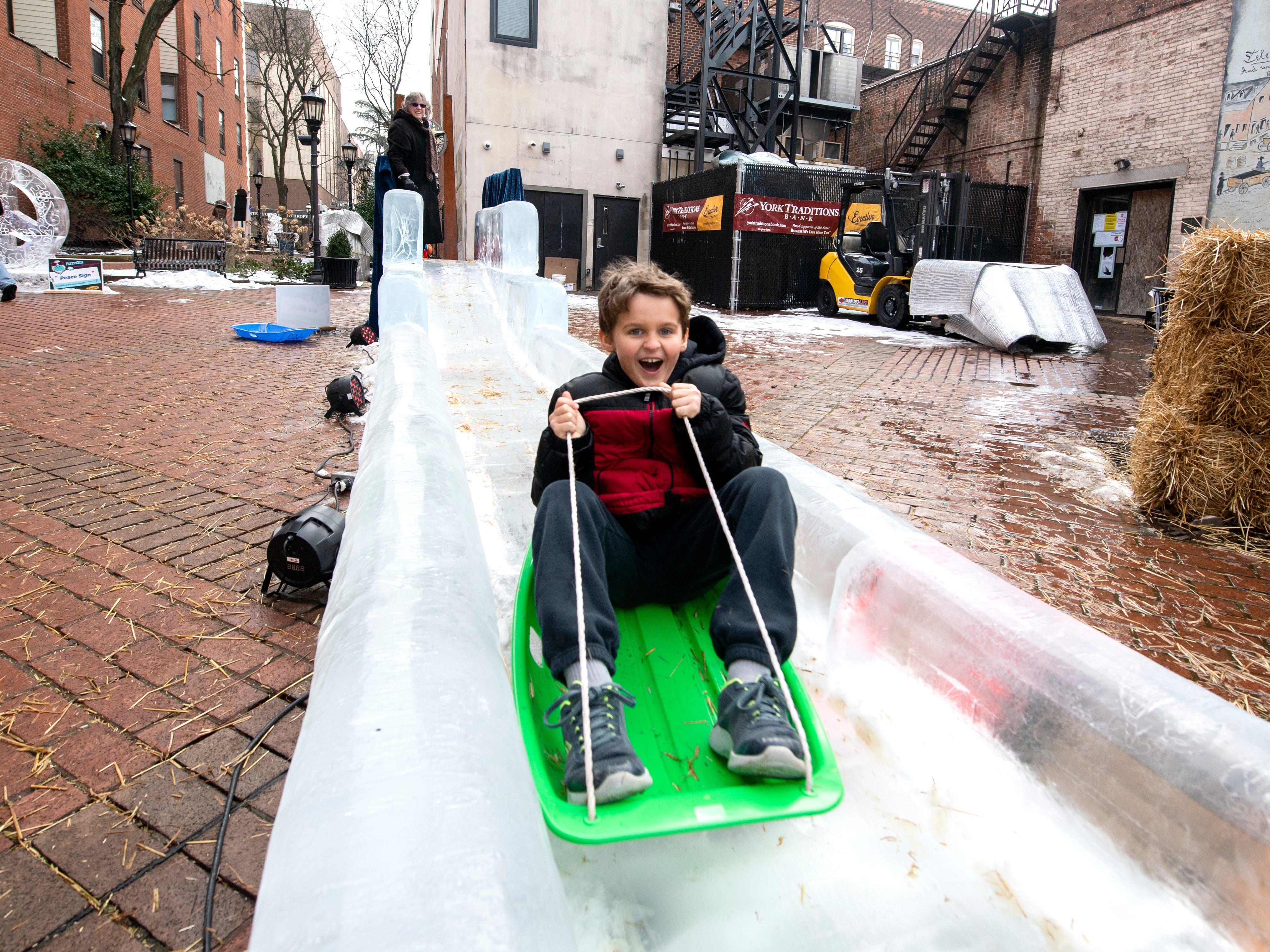 Ozzie Davidson, 7, of Hellam Township, rides down the ice slide in Cherry Lane, downtown, Friday. The FestivICE festival has interactive ice sculptures, a slide and more. The three-day event ends Saturday.