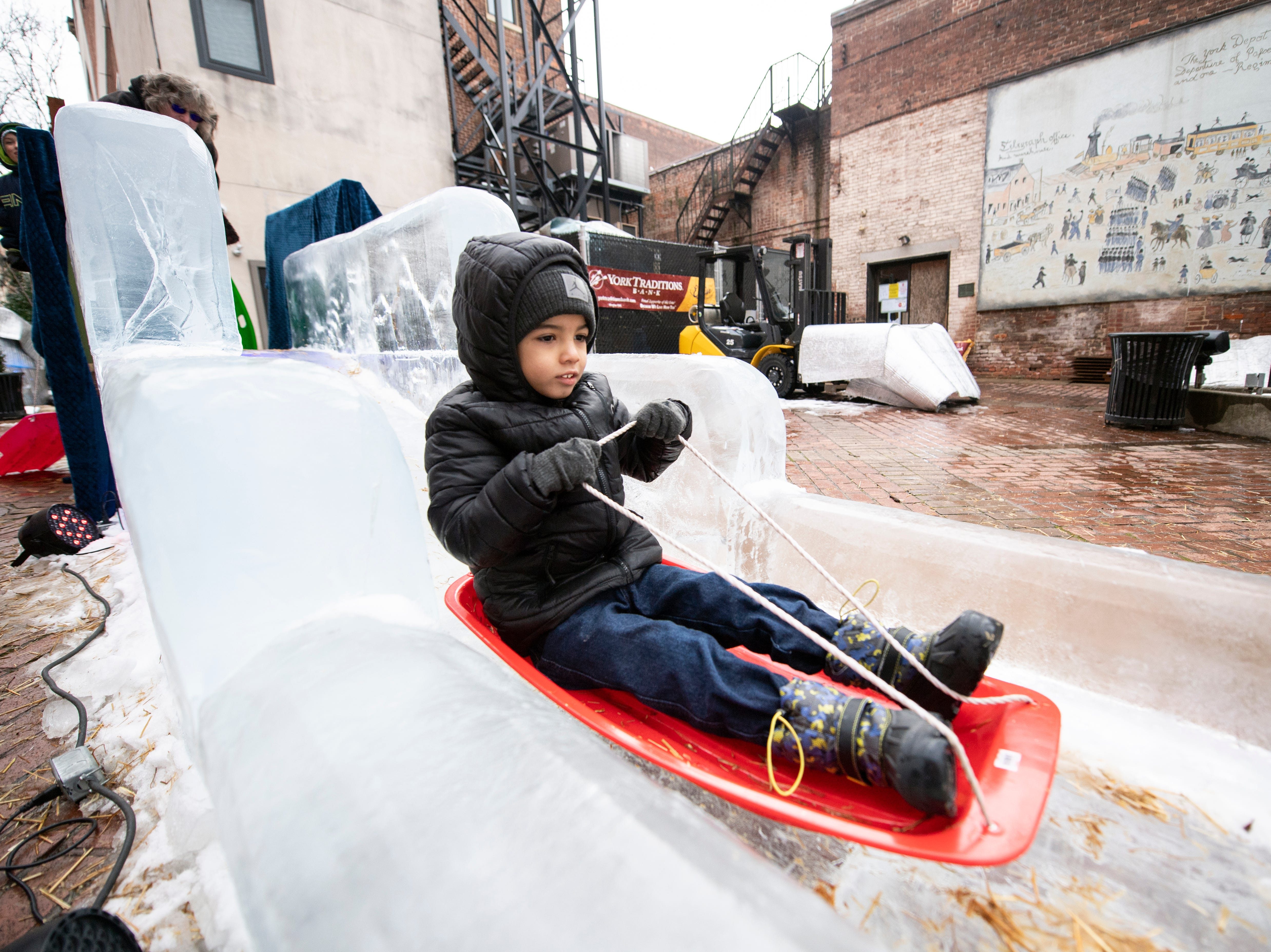 Jayvon Claw, 5, rides a sled down the 40-foot ice slide in Cherry Lane, downtown, Friday, Jan. 18, 2019. The FestivICE ice festival has interactive ice sculptures, an ice slide and more. The three-day event ends Saturday.