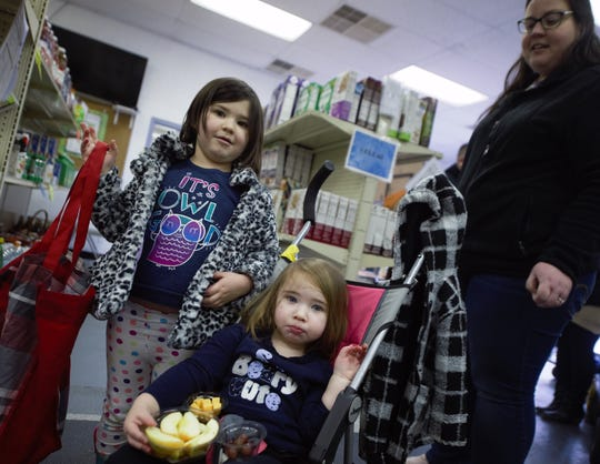 Left to right: Jordan Fink, 4 and her sister Mia, 2, wait in line with their mother, Becca Fink of Hanover, at the York County Food Bank. The family found itself in need of help during the government shutdown.