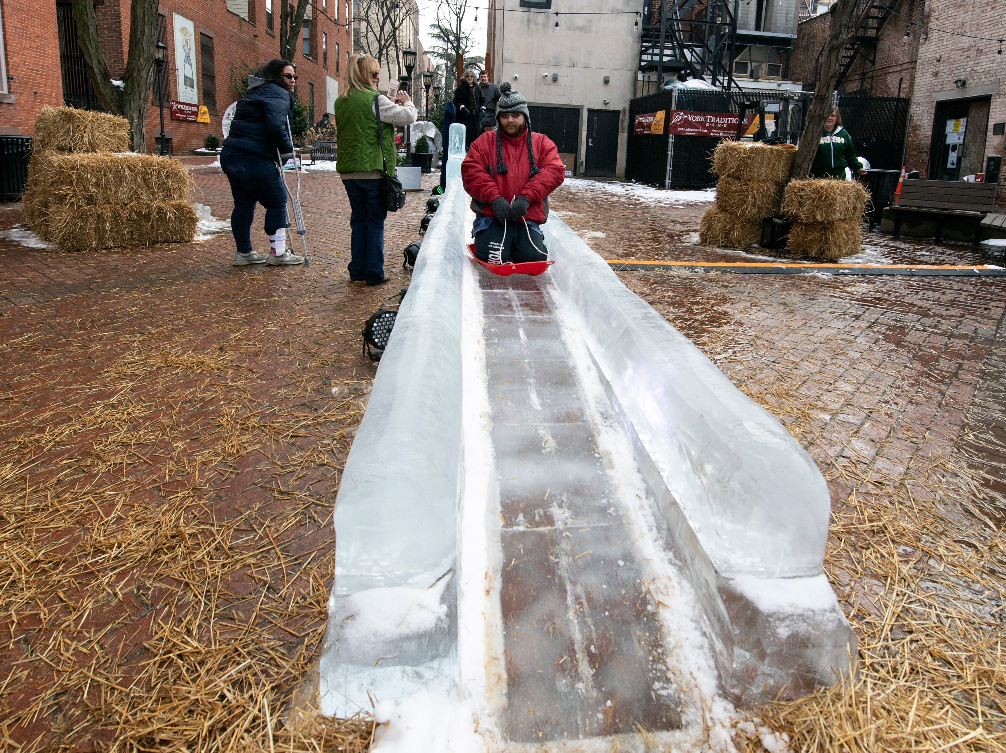 Dan Schultheiss rides a sled down the 40-foot ice slide in Cherry Lane, downtown, Friday, Jan. 18, 2019. The FestivICE ice festival has interactive ice sculptures, an ice slide and more. The three-day event ends Saturday.