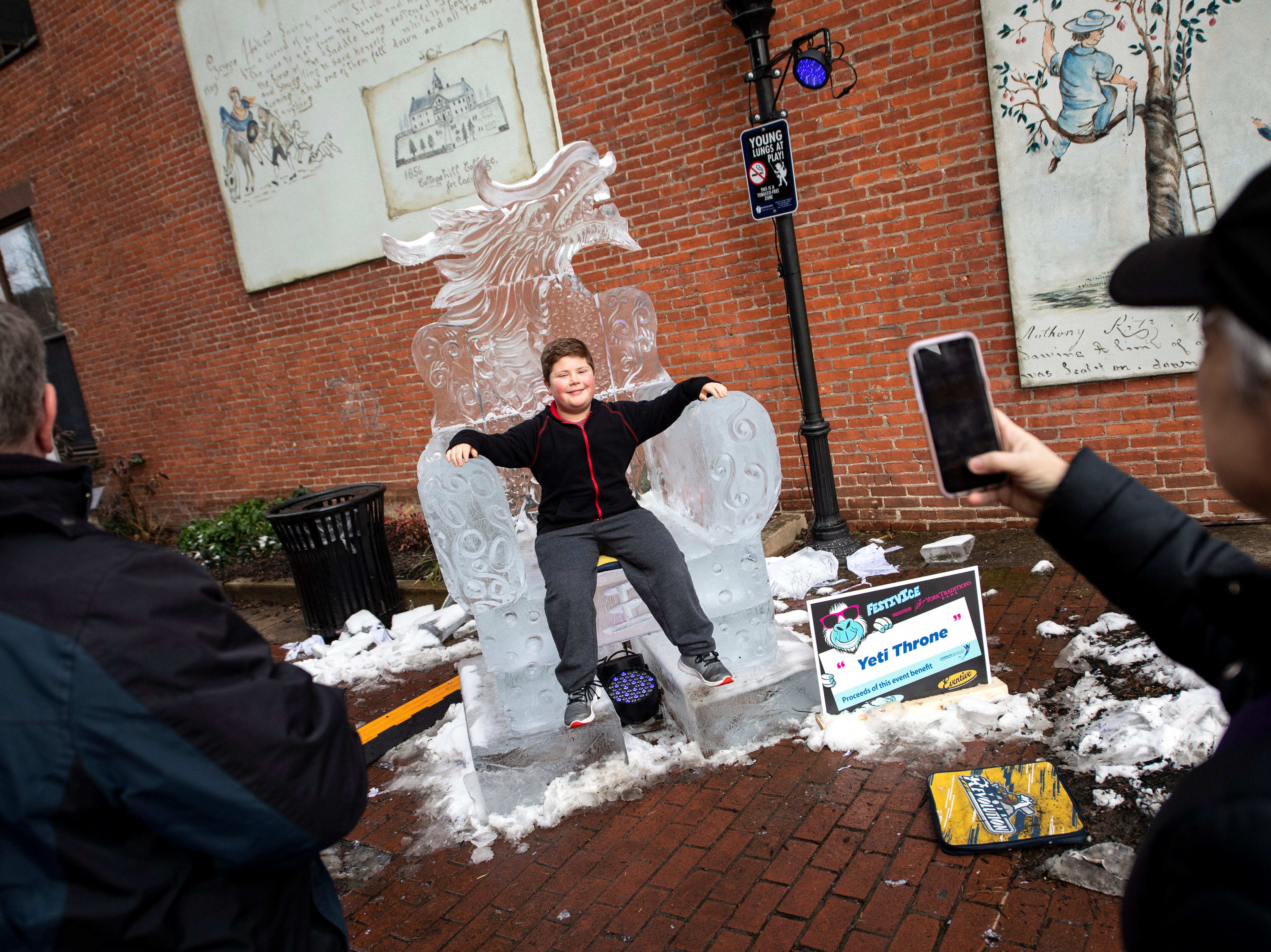 """Hayden Brandt, 11, of East York, sits in the """"Yeti Throne"""" in Cherry Lane, Friday, Jan. 18, 2019. The FestivICE ice festival has interactive ice sculptures, an ice slide and more. The three-day event ends Saturday."""