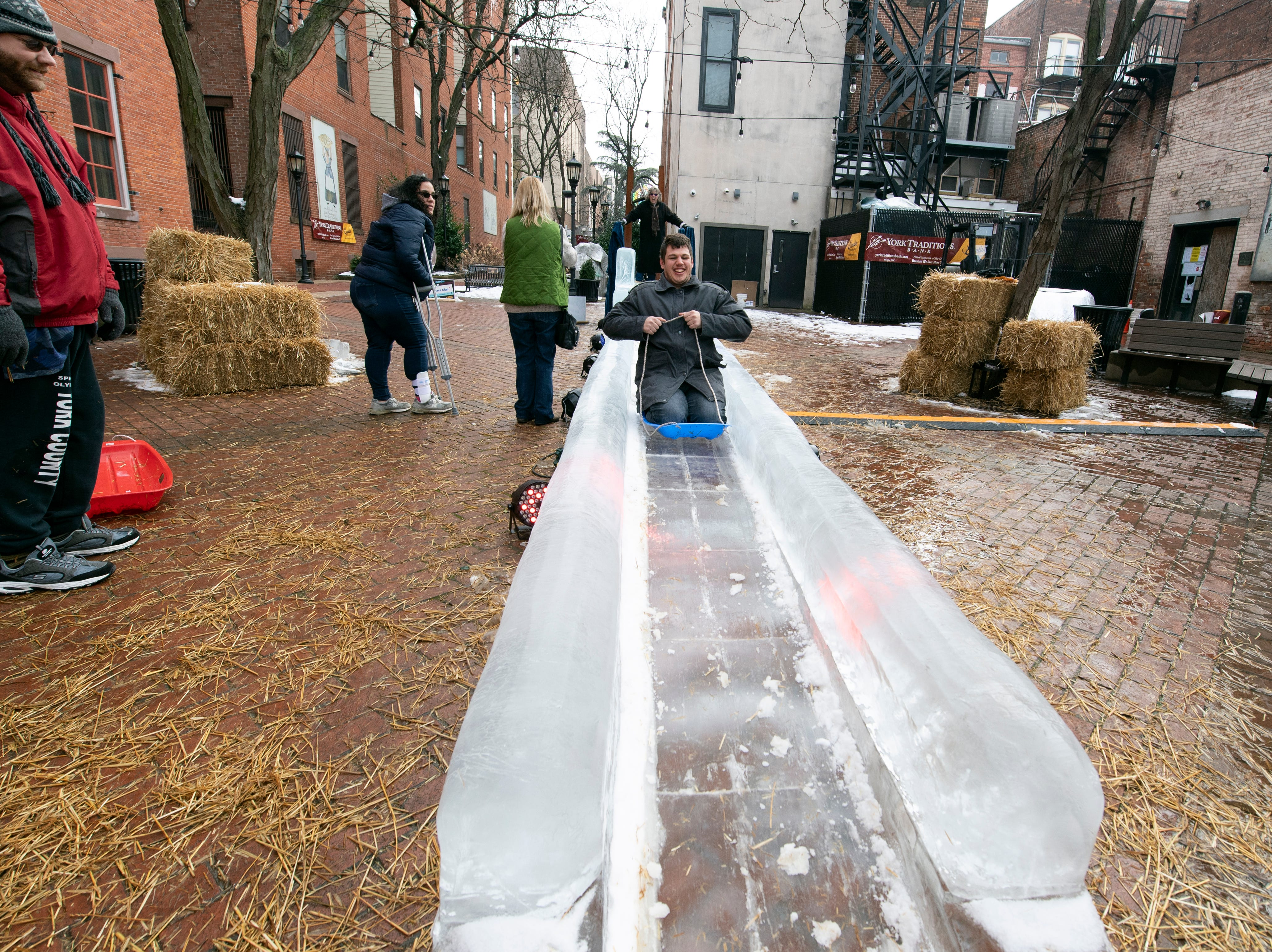Stephen Lichty rides a sled down the 40-foot long ice slide in Cherry Lane, downtown, Friday, Jan. 18, 2019. The FestivICE ice festival has interactive ice sculptures, an ice slide and more. The three-day event ends Saturday.