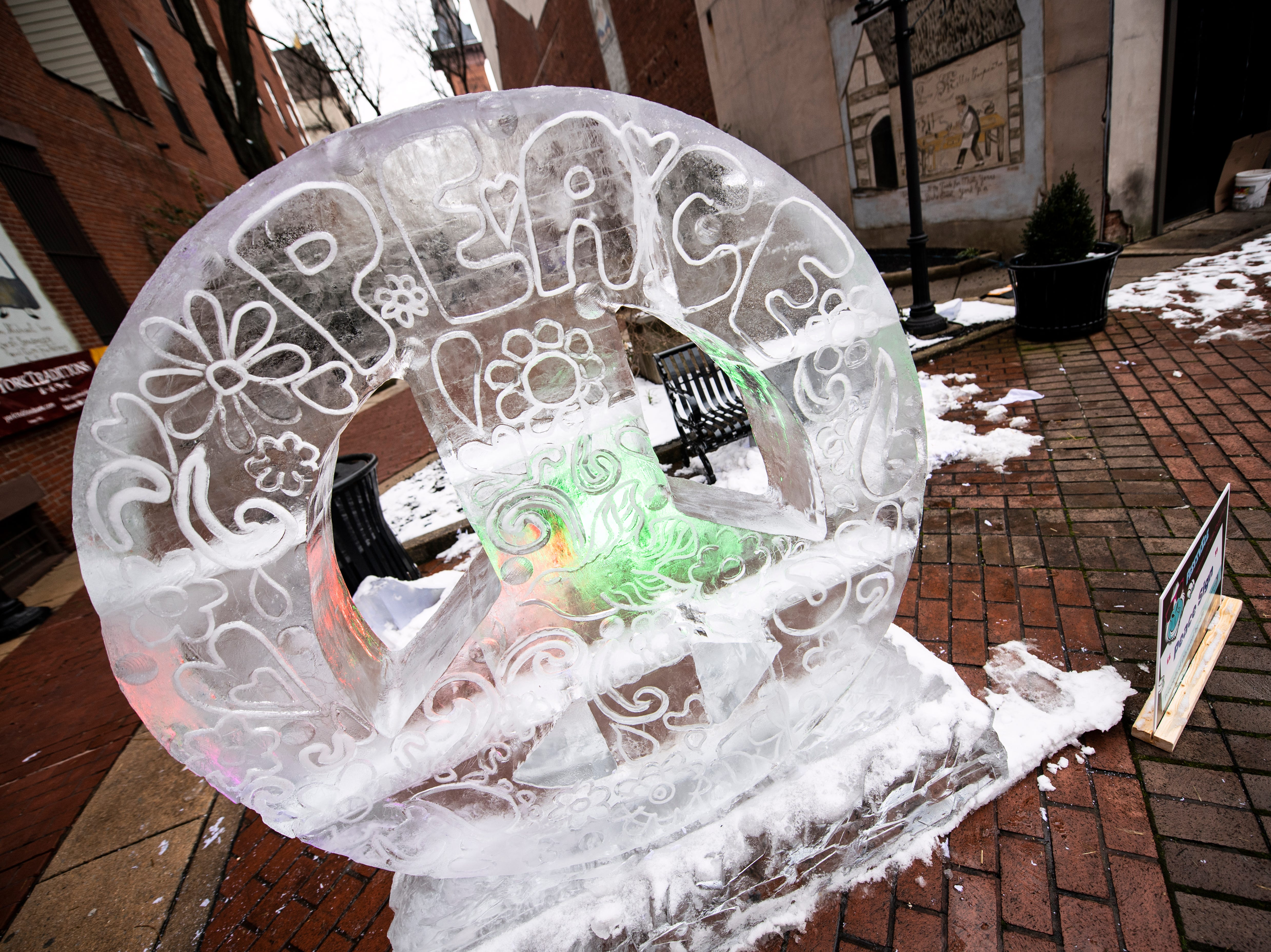 The 'peace sign' sculpture, decked out with lights, is one of more than a dozen ice sculptures in and around Cherry Lane, Friday, Jan. 18, 2019. The FestivICE ice festival has interactive ice sculptures, an ice slide and more. The three-day event ends Saturday.
