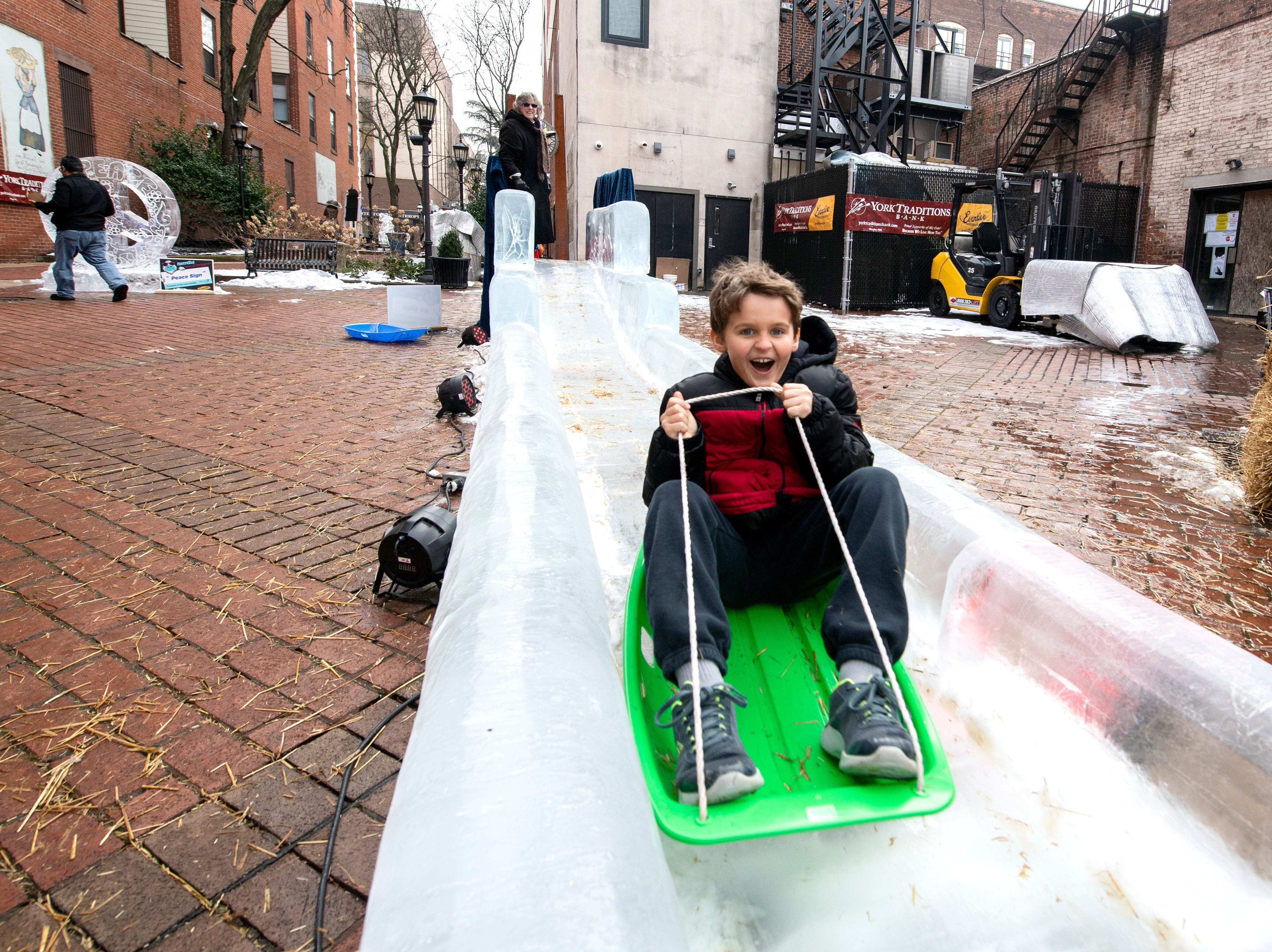 Ozzie Davidson, 7, of Hellam, rides down the ice slice in Cherry Lane, downtown, Friday, Jan. 18, 2019. The FestivICE ice festival has interactive ice sculptures, an ice slide and more. The three-day event ends Saturday.
