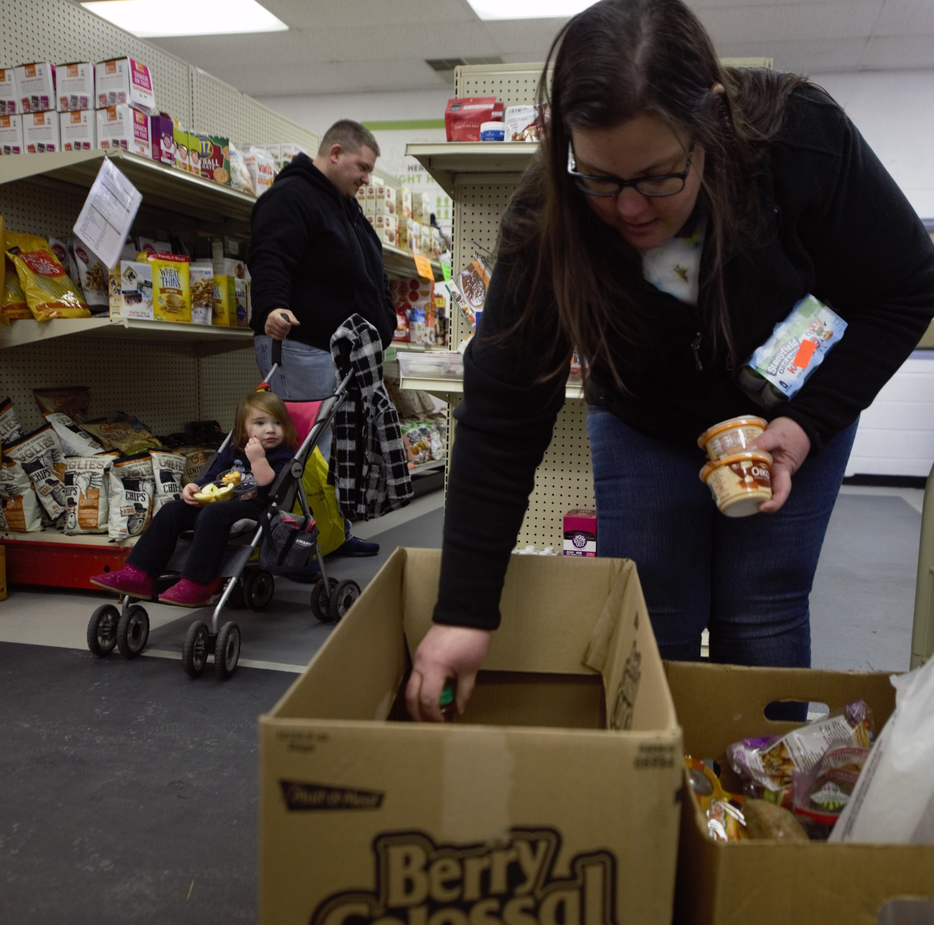 Becca Fink of Hanover loads up a box of food at the York County Food Bank. Fink's husband Stephen works for the Dept. of Commerce and with the shutdown entering its 28th day the family has been forced to rely on local food banks within the area.