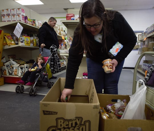 Becca Fink of Hanover loads up a box of food at the York County Food Bank. Fink's husband, Stephen, works for the Department of Commerce, and with the shutdown now over a month old, the family has been forced to rely on local food banks within the area.