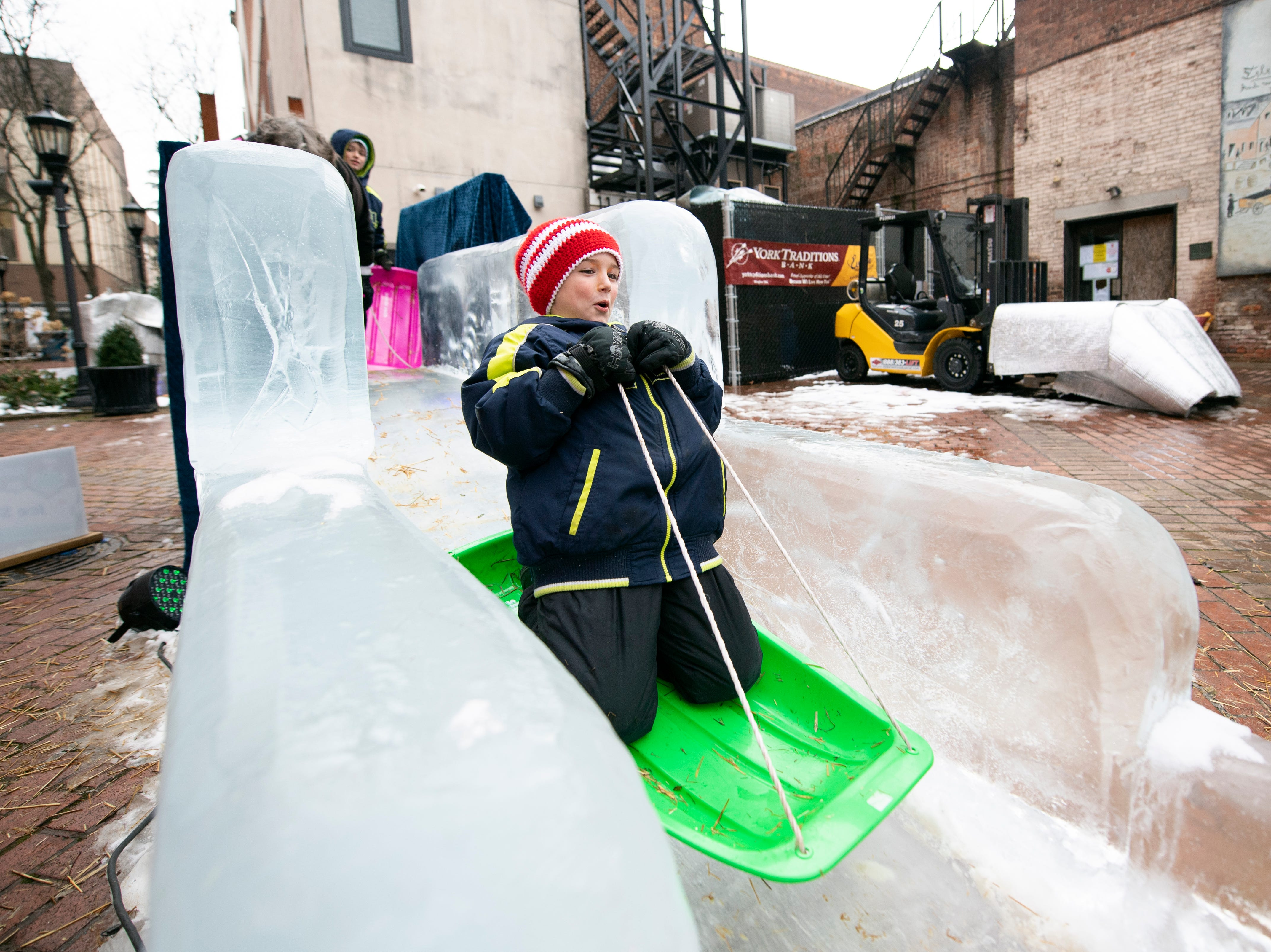 Dyllan Arnold, 6, of East York, rides a sled down the 40-foot ice slide in Cherry Lane, downtown, Friday, Jan. 18, 2019. The FestivICE ice festival has interactive ice sculptures, an ice slide and more. The three-day event ends Saturday.